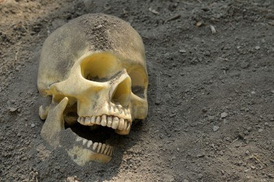3616760-human-skull-half-buried-in-the-earth